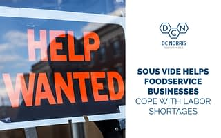 help wanted sign hanging in the window next to the blog title commercial sous vide equipment helps foodservice businesses cope with labor shortages