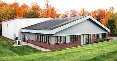 exterior view of the new DC Norris North America office in Traverse City, Michigan. A grey building with large windows and a lower brick accent.