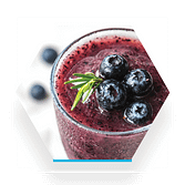 image of a blueberry based smoothie in a clear glass with a sprig of rosemary