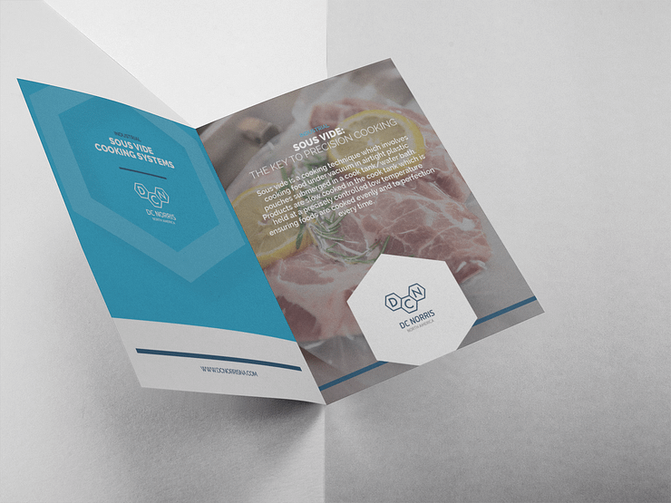 DC Norris North America's sous vide cooking systems brochure open against a grey background showing steak ready to be cooked in a sous vide cook tank